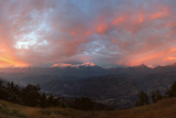A Distant View of the Cordillera Blanca with Orange and Pink Clouds in the Sky