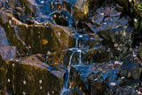 A Waterfall Trickles over Granite Rocks Covered with Leaves in the Fall