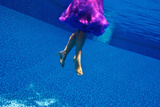 A Model Floats in a Pool  Wearing a Skirt and Heels