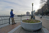 A Man Fishes in New York City's East River with His Dog