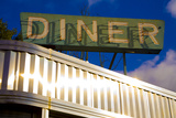 An Old Neon Diner Sign Above Glistening Reflective Aluminum Siding