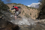 A Mountain Biker Blasts Through a Stream in the Mountains of Nepal