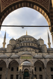 Blue Mosque under a Partially Cloudy Sky Through an Ornate Archway