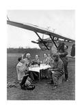Flugpassagiere während einer Rast neben dem Flugzeug  1930