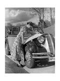 Eine Frau entfaltet eine Straßenkarte auf der Motorhaube eines BMW 329  1938