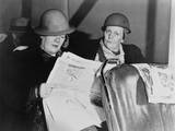After Working All Night  Two Helmeted Women Shipyard Workers Read the Newspaper on the Bus Home