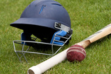 Cricket Ball  Bat and Helmet on Green Grass of Cricket Pitch