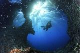 Scuba Diver Swimming through an Arch