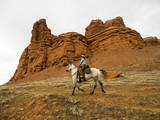 Cowgirl at Full Gallop with Red Rock Hills