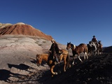 Riders and Horses with Shadows Coming down Hill in Painted Desert