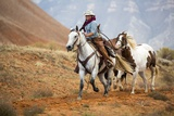 Cowgirl at Full Gallop with Horses in Tow