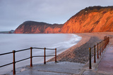 Early Morning Sunlight Glows Against the Distinctive Red Cliffs of High Peak  Sidmouth  Devon