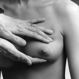 A Female Nude from the Waist Up with a Doctors Hands Conducting a Clinical Breast Examination