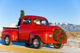 Santa Driving a Vintage Red Ford Pick-Up Truck Down a Snowcovered Rural Road