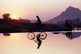 Bicyclist Crossing Shallow River at Sunset with Women in Background Doing Washing