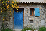 A Stone Building with a Bright Blue Door and Window Shutter