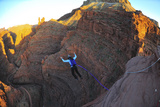 A Woman Base Jumps with a Parachute Off a Desert Spire on Fisher Towers