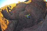 A Man Base Jumps with a Parachute Off a Desert Spire on Fisher Towers