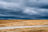 A Deserted Highway Cuts Through a Picturesque Landscape Beneath a Stormy Sky