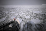 A Person Stands on the Bow of a Cruise Ship as it Plows Through Pack Ice