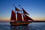A Sailboat Carrying Tourists Returns to Port after a Sunset Sail