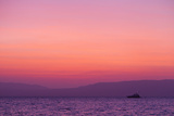 Sunset Turns the Sky Pink and Purple as a Lone Boat Floats Offshore