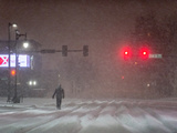 A Man Walking to Work Waits for a Red Light During a Predawn Snowstorm