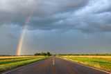 A Thunderstorm Produces a Vivid Rainbow Next to a Rain-Soaked Paved Road