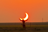 Woman Holds Up Arms as If She Is Holding Up the Annular Solar Eclipse