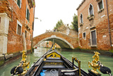 A View of Buildings and a Bridge from the Prow of Gondola in a Side Canal of Venice