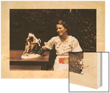 A Young Woman Sits at a Table and Admires a Small Statue of Animals
