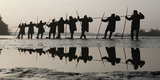 Fishermen Pull a Net Containing Fish from a Lake