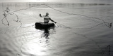 Fisherman Floating on a Rubber Tube Throws a Net to Catch Fish  Sabarmati River in Ahmedabad