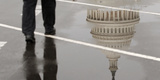 The Dome of the US Capitol Building Is Reflected in a Puddle on a Rainy Morning in Washington