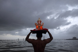 A Devotee Carries a Statue of the Hindu God Ganesh into the Arabian Sea