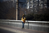A Woman Wearing a Skull Mask Stands on a Bridge in Central Beijing