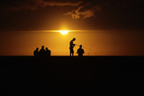 Fishermen Stand on Havana's Seafront Boulevard El Malecon as the Sun Sets