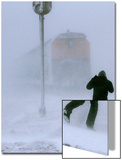 A Man Crosses a Railway Track During Heavy Snowfall