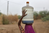 Village Woman Carries Container Filled with Drinking Water Supplied by Government-Run Water Tanker