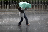 A Woman Struggles to Hold an Umbrella as She Walks Through a Storm in Beijing