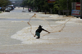 A Man Casts a Fishing Net into Floodwaters