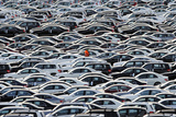 A Worker Walks Along Rolls of Mercedes Cars
