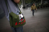 A Man Carries a Bag with a Picture of Former Chinese Leader Mao Zedong