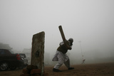 A Man Plays Cricket Amid Heavy Fog in New Delhi