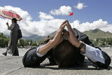 A Tibetan Pilgrim Prays in Front of the Potala Palace in Lhasa in Tibet