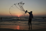 A Palestinian Fisherman Throws His Net During Sunset in Gaza City