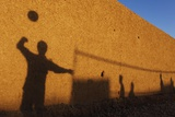 Shadows are Cast on a Wall by Afghan Soldiers Playing Volleyball