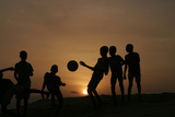 Children Playing Soccer are Silhouetted at Sunset in Nigeria's Main City of Lago