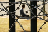 A Boy Sits in a Park Surrounded by Razor Wire in Pretoria