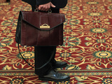 A Man Holds His Briefcase While Waiting in Line During a Job Fair in Melville  New York